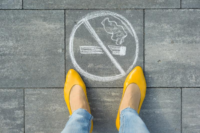 Female feet with picture no smoking painted on the grey sidewalk.  stock photos