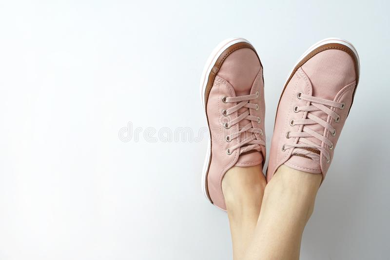 Female feet in pink snickers on white background. Brand new pink shoes royalty free stock image