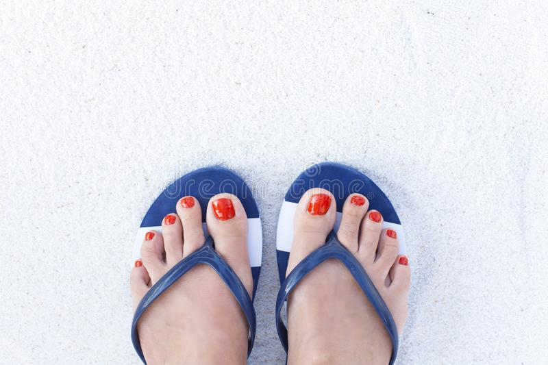 Female feet on sand. Woman feet wearing flip flops on a beach stock photo