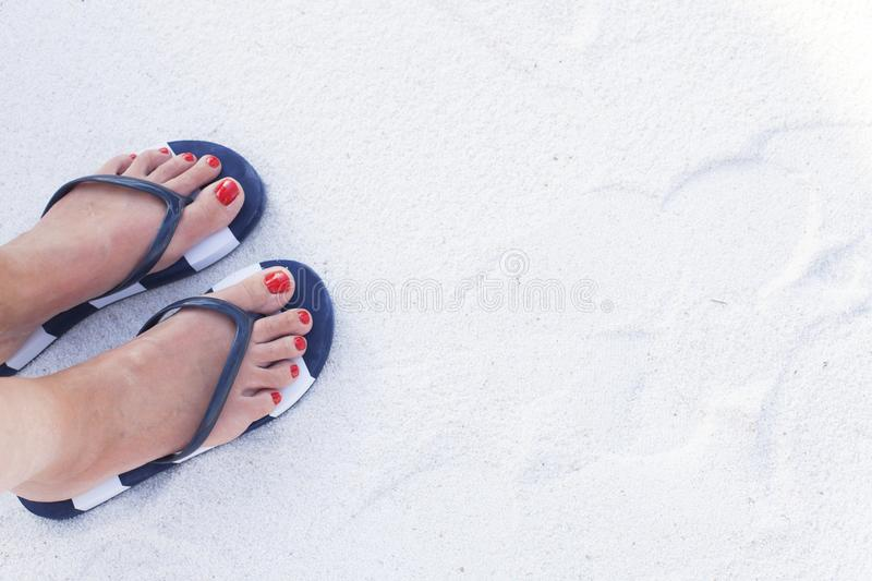 Female feet on sand. Woman feet wearing flip flops on a beach stock images