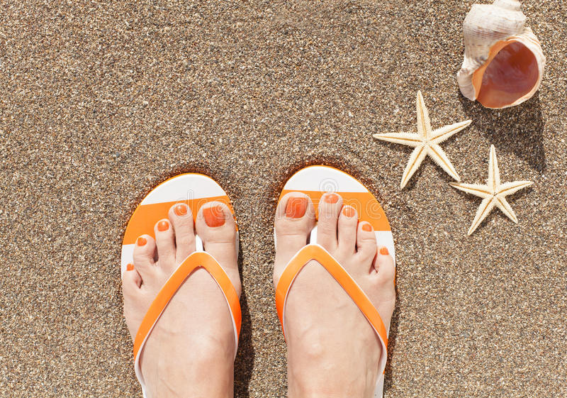 Female feet on sand. Woman feet wearing flip flops on a beach stock image