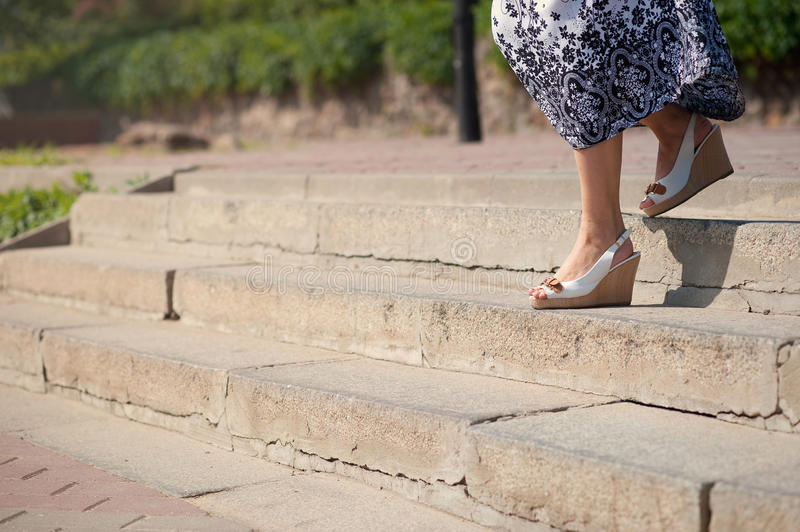 Female feet in sandals on the top of big steps down. Long pathway downstairs stock photo