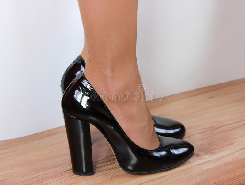 Female feet shod in black shoes with heels on a white background standing on the wooden floor stock photo