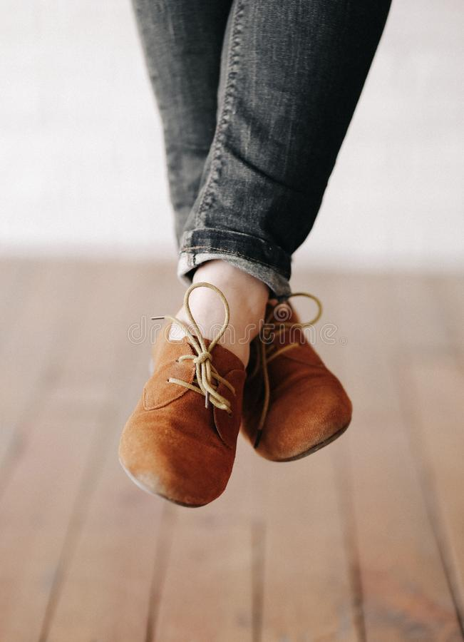 Female feet shoes laces not touching floor. Female feet in shoes with laces not touching the floor stock images