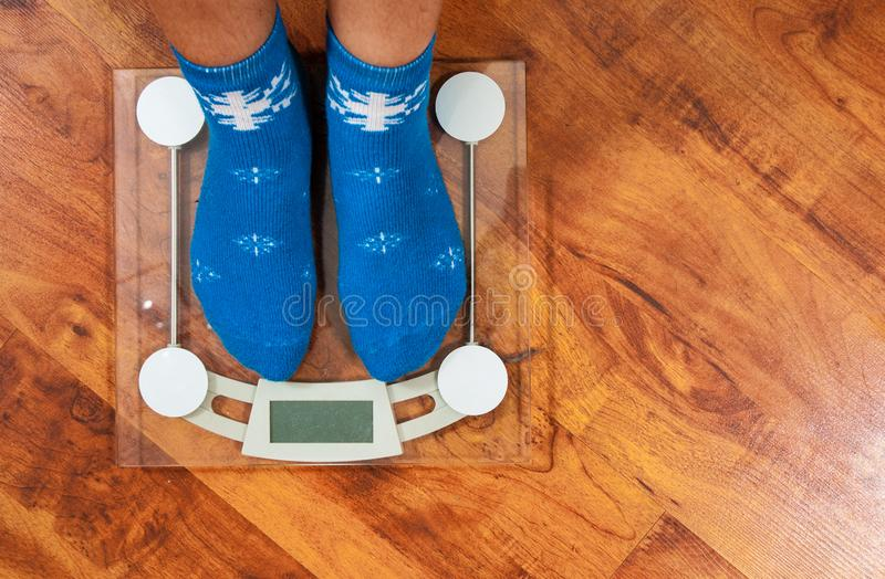 Female feet standing on electronic scales for weight control in Christmas socks on wooden floor background. with copy space. stock photos