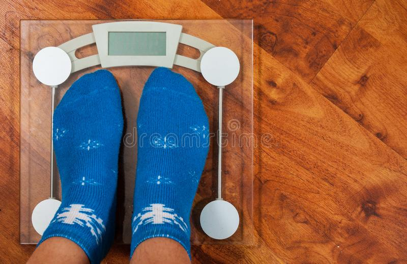 Female feet standing on electronic scales for weight control in Christmas socks on wooden floor background. with copy space. stock image