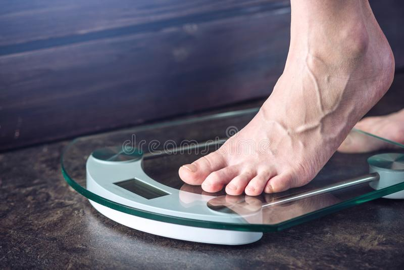Female feet standing on electronic scales for weight control on dark background. Concept of sports training, diets. Female feet standing on electronic scales for royalty free stock images