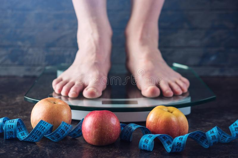 Female feet standing on electronic scales for weight control on dark background. Concept of sports training, diets. Female feet standing on electronic scales for stock image