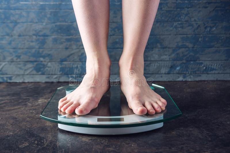 Female feet standing on electronic scales for weight control on dark background. Concept of sports training, diets. Female feet standing on electronic scales for royalty free stock photography