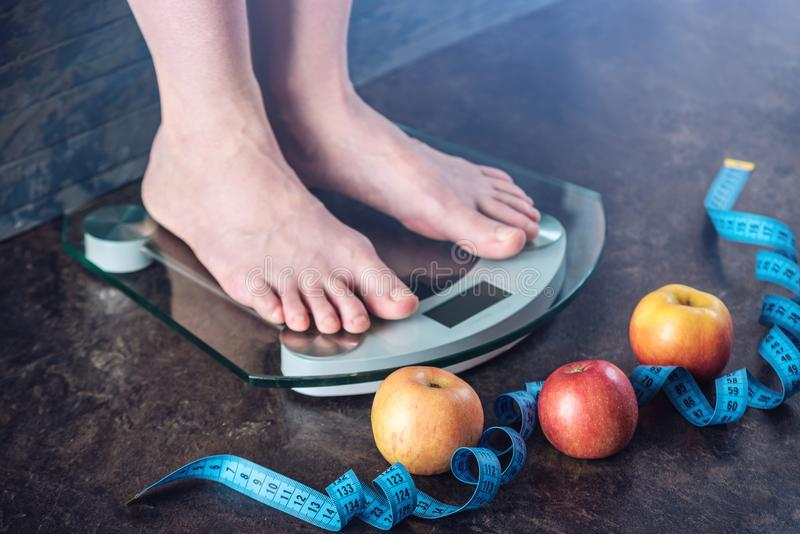 Female feet standing on electronic scales for weight control on dark background. Concept of sports training, diets. Female feet standing on electronic scales for stock photos