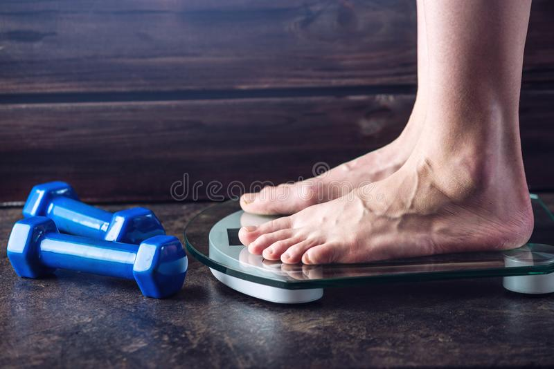 Female feet standing on electronic scales for weight control on dark background. Concept of sports training, diets. Female feet standing on electronic scales for stock photo