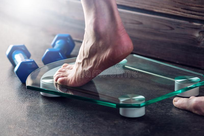 Female feet standing on electronic scales for weight control on dark background. Concept of sports training, diets. Female feet standing on electronic scales for royalty free stock photo