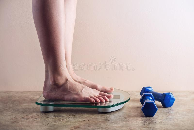 Female feet standing on electronic scales for weight control on light background. Concept of sports training, diets. Female feet standing on electronic scales stock photo