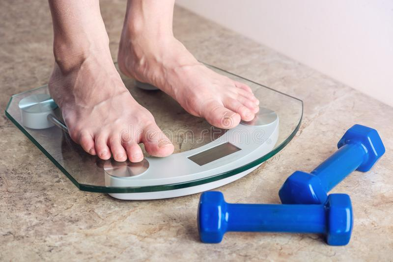 Female feet standing on electronic scales for weight control on light background. Concept of sports training, diets. Female feet standing on electronic scales royalty free stock image