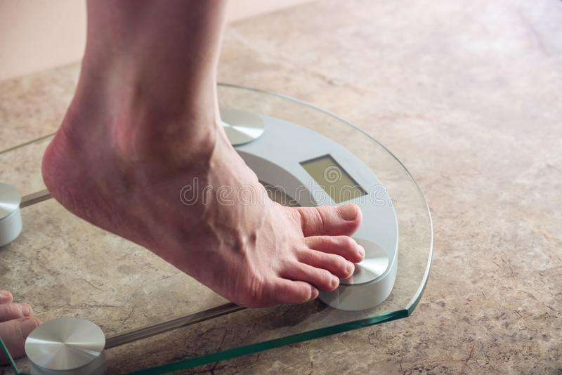 Female feet standing on electronic scales for weight control on light background. Concept of sports training, diets. Female feet standing on electronic scales royalty free stock photos