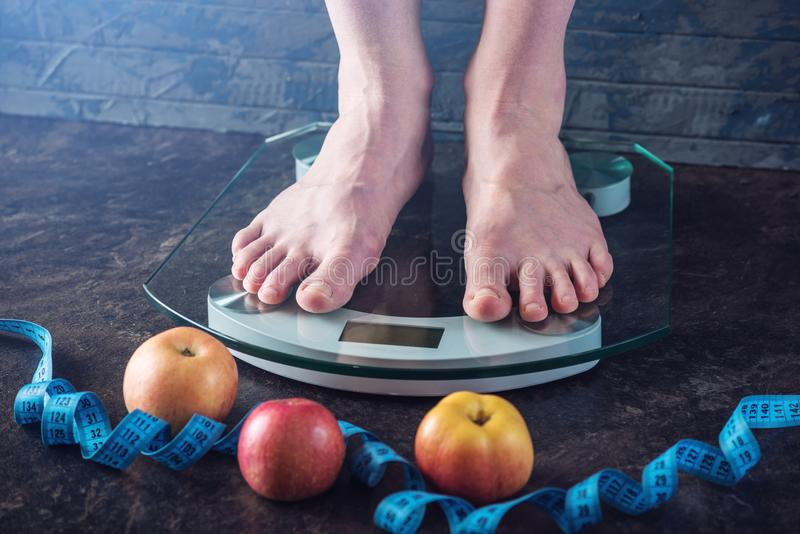 Female feet standing on electronic scales for weight control on dark background. Concept of sports training, diets. Female feet standing on electronic scales for stock photography