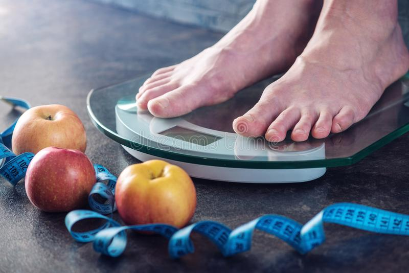 Female feet standing on electronic scales for weight control on dark background. Concept of sports training, diets. Female feet standing on electronic scales for royalty free stock photos
