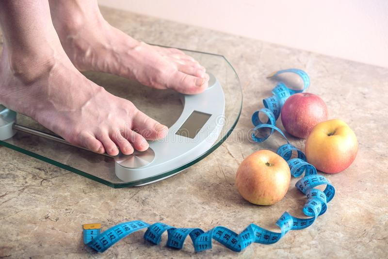 Female feet standing on electronic scales for weight control on light background. Concept of sports training, diets. Female feet standing on electronic scales stock photography