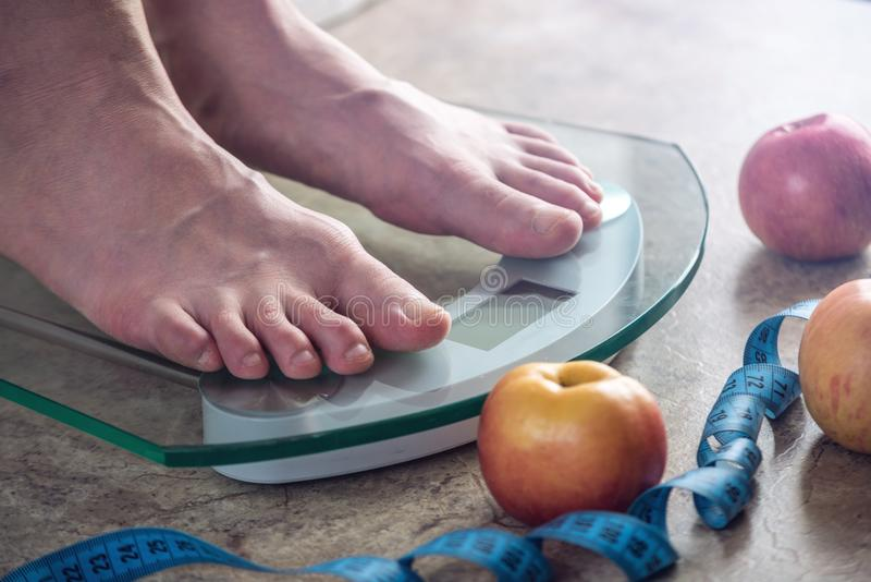 Female feet standing on electronic scales for weight control on light background. Concept of sports training, diets. Female feet standing on electronic scales stock image