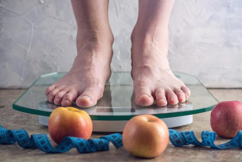 Female feet standing on electronic scales for weight control on light background. Concept of sports training, diets. Female feet standing on electronic scales royalty free stock photography