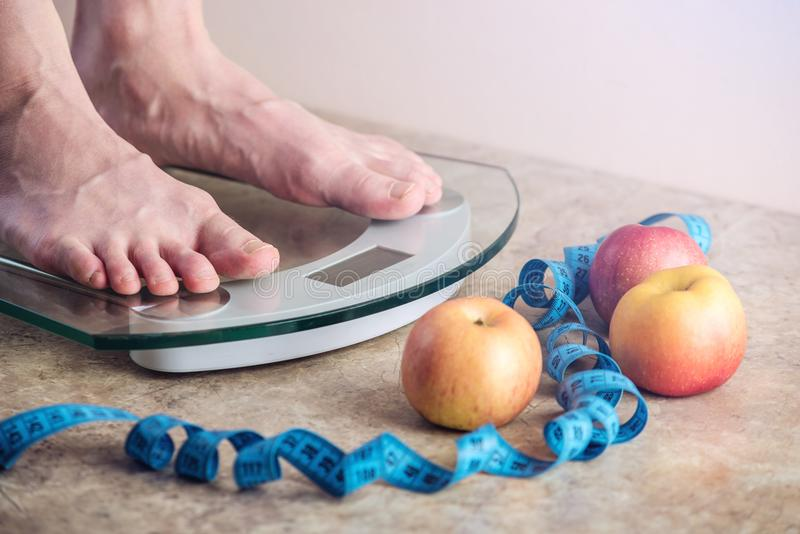 Female feet standing on electronic scales for weight control on light background. Concept of sports training, diets. Female feet standing on electronic scales stock photos