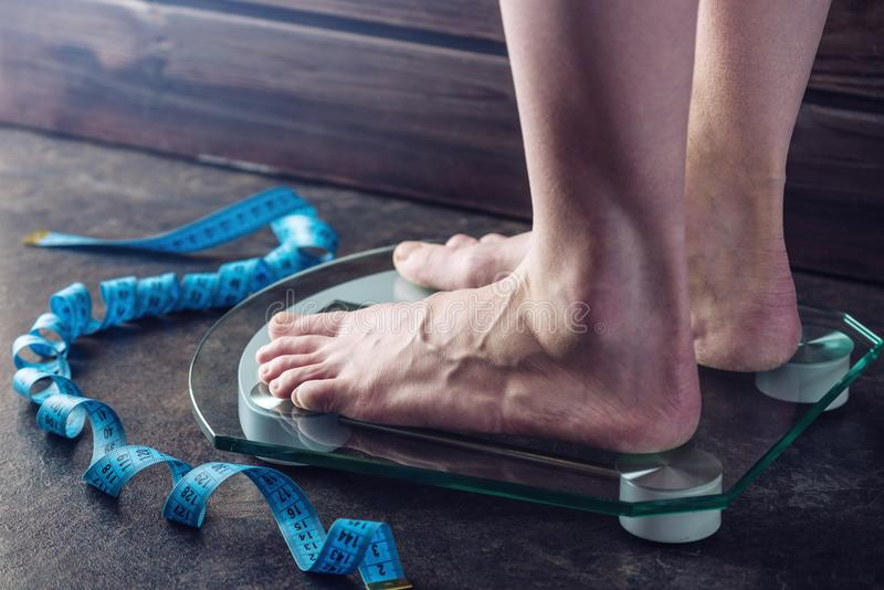 Female feet standing on electronic scales for weight control on dark background. Concept of sports training, diets. Female feet standing on electronic scales for royalty free stock image
