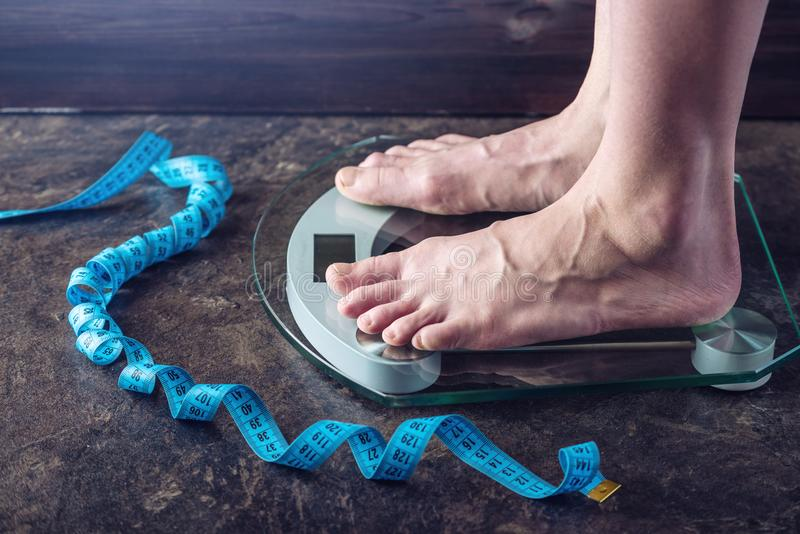 Female feet standing on electronic scales for weight control on dark background. Concept of sports training, diets. Female feet standing on electronic scales for stock images
