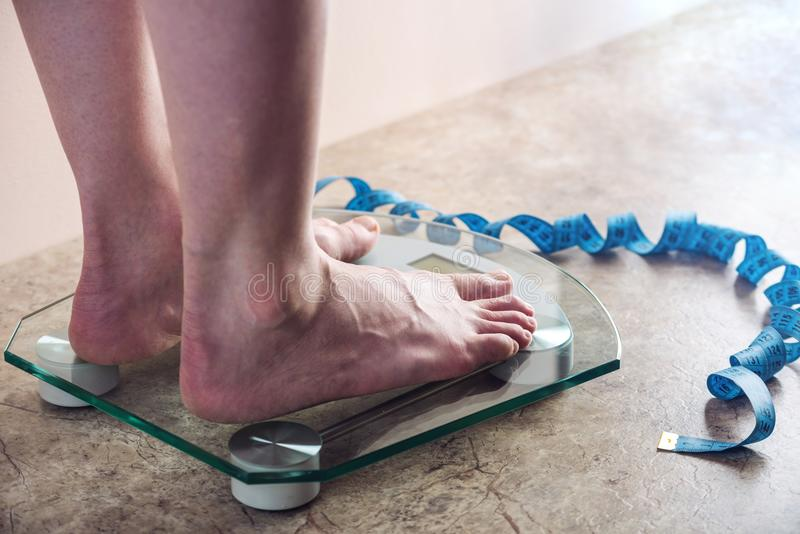 Female feet standing on electronic scales for weight control on light background. Concept of sports training, diets. Female feet standing on electronic scales stock images