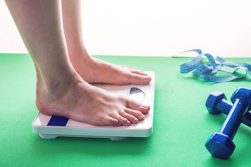 Female feet standing on mechanical scales, dumbbells and measuring tape. Concept of slimming and weight loss royalty free stock photos