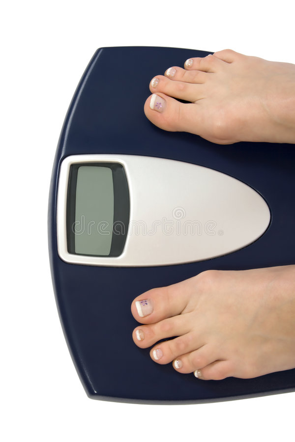 Female feet standing on scale royalty free stock images
