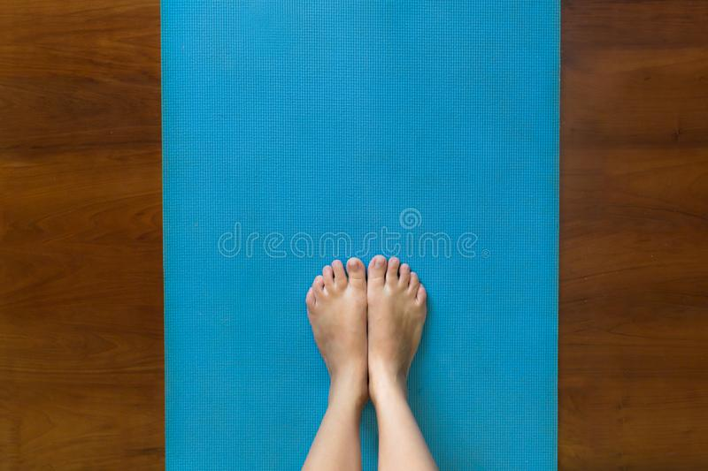 Woman standing on a yoga mat at home royalty free stock photos
