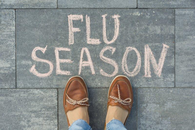 Female feet with text flu season written on grey sidewalk.  stock images