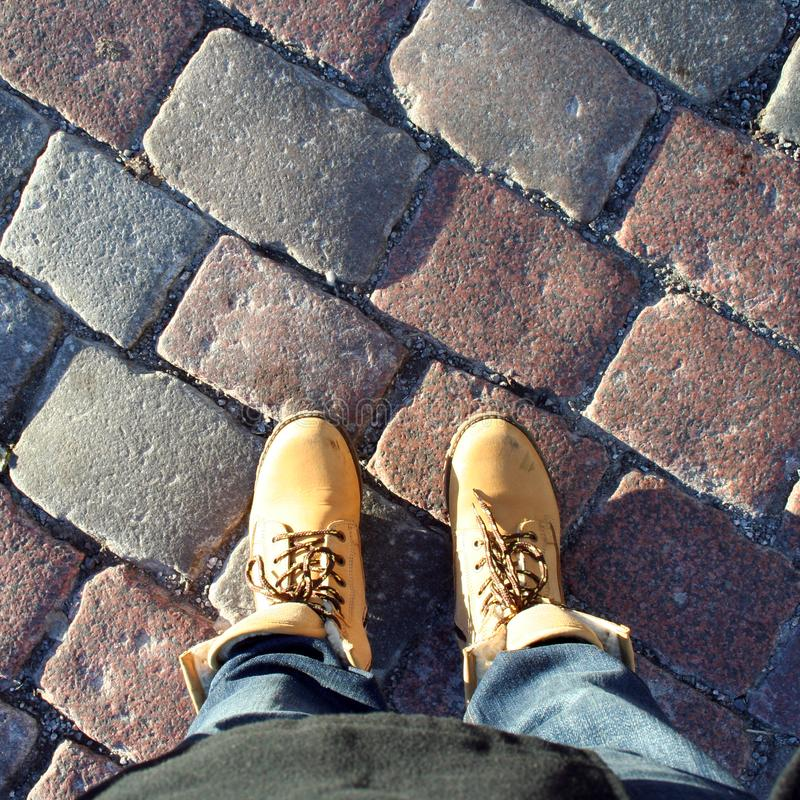 Female feet in track shoes on cobblestone. Female feet in track orange winter shoes on cobblestone, city toutrism concept royalty free stock photo