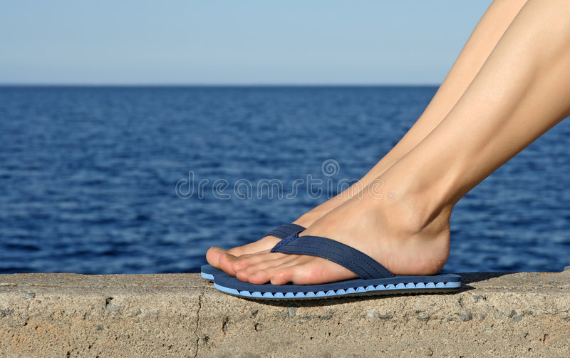Female feet wearing blue flip-flops royalty free stock image