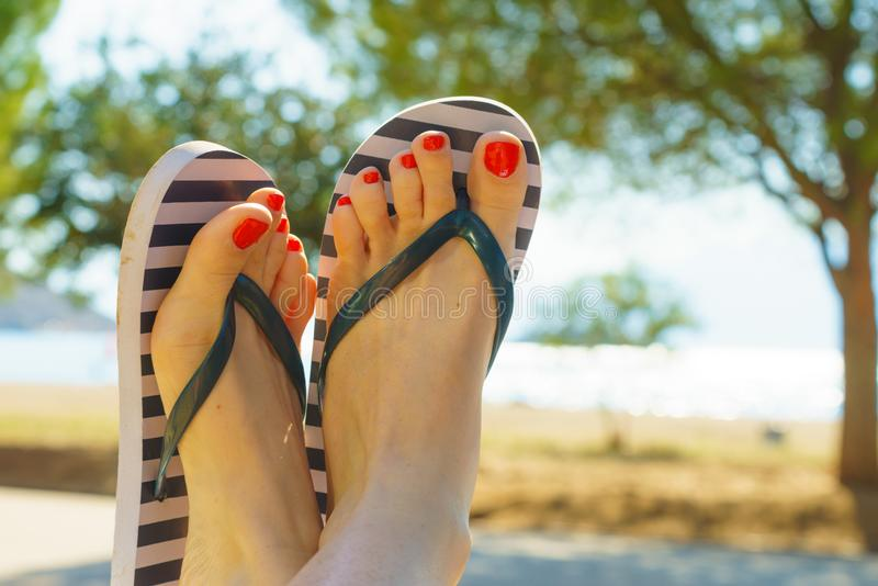 Female feet wearing flip flops having red nails. Unrecognizable woman wearing stripped flip flops and having painted toes with red nail polish. Female relaxing royalty free stock image