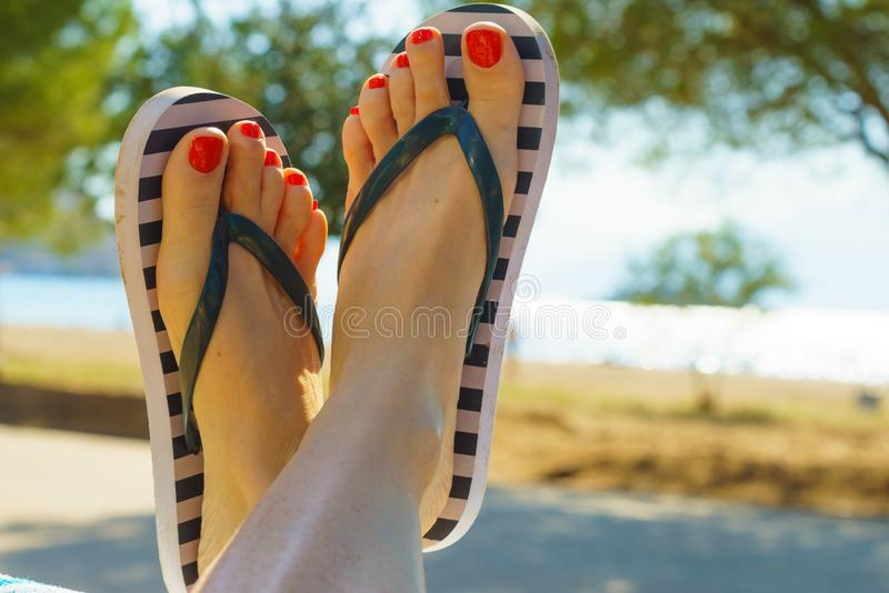Female feet wearing flip flops having red nails. Unrecognizable woman wearing stripped flip flops and having painted toes with red nail polish. Female relaxing stock photo