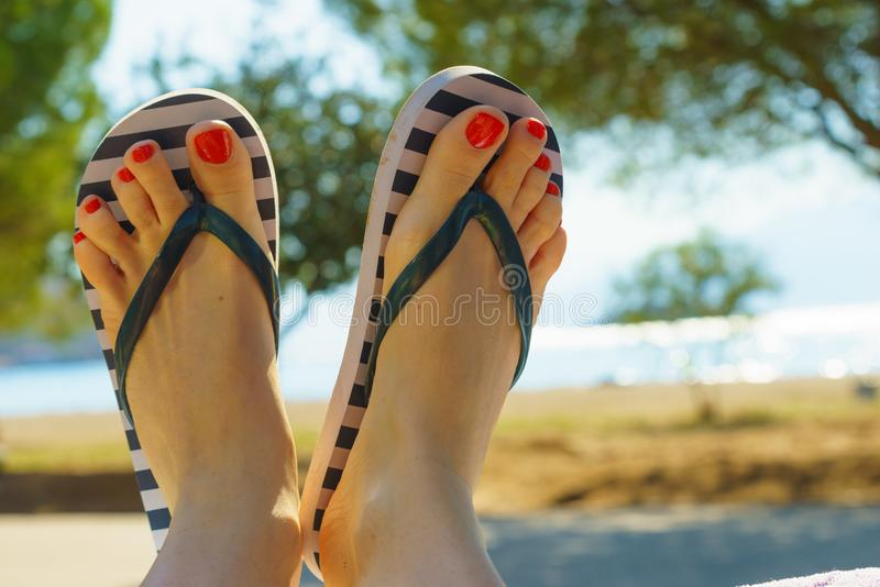 Female feet wearing flip flops having red nails. Unrecognizable woman wearing stripped flip flops and having painted toes with red nail polish. Female relaxing royalty free stock photo