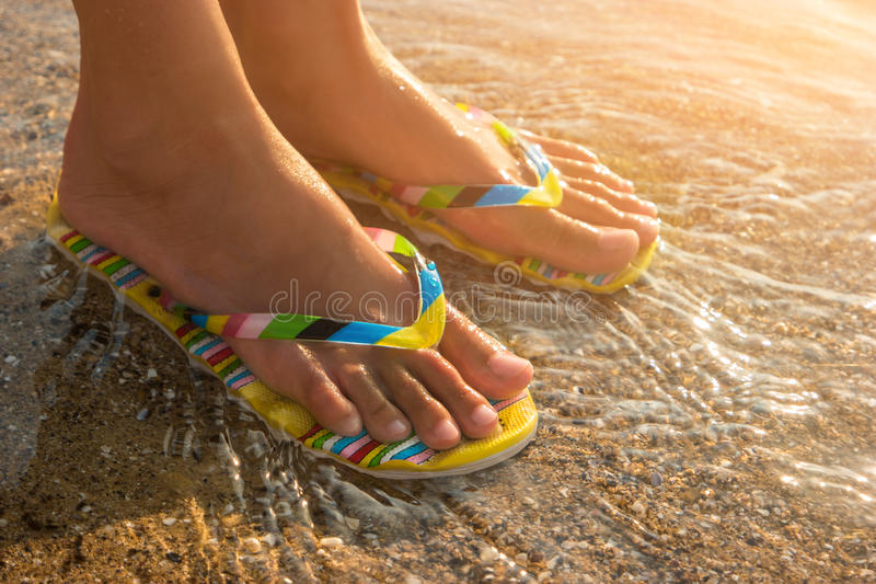 Female feet wearing flip flops. Water and sand under sunlight. One step away from sea. Visit a tropical island stock images