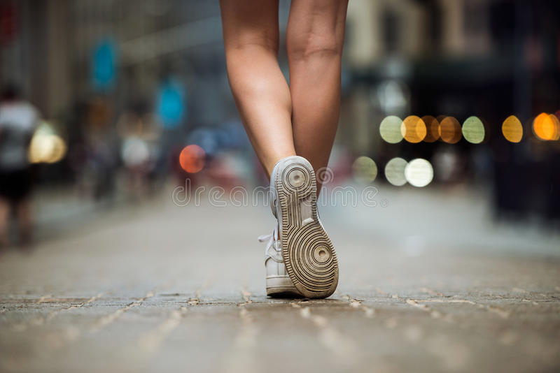 Female feet wearing sneakers running in city street. Woman with beautiful legs running in city at morning stock photography
