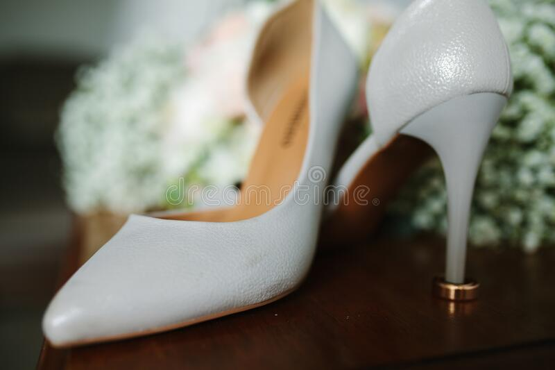 Female feet in white wedding sandals with a bouquet of camomiles.  royalty free stock images