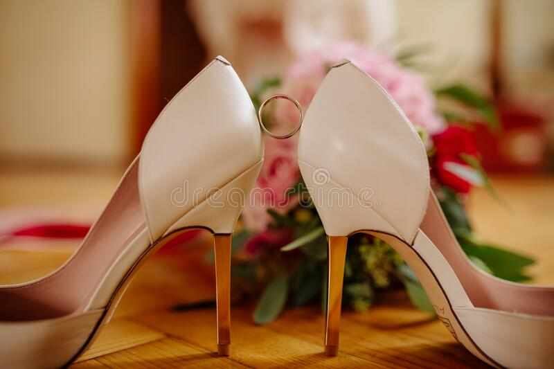 Female feet in white wedding sandals with a bouquet of camomiles.  royalty free stock image