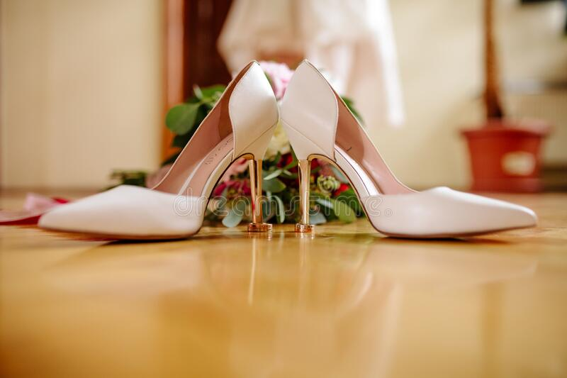Female feet in white wedding sandals with a bouquet of camomiles.  royalty free stock photo