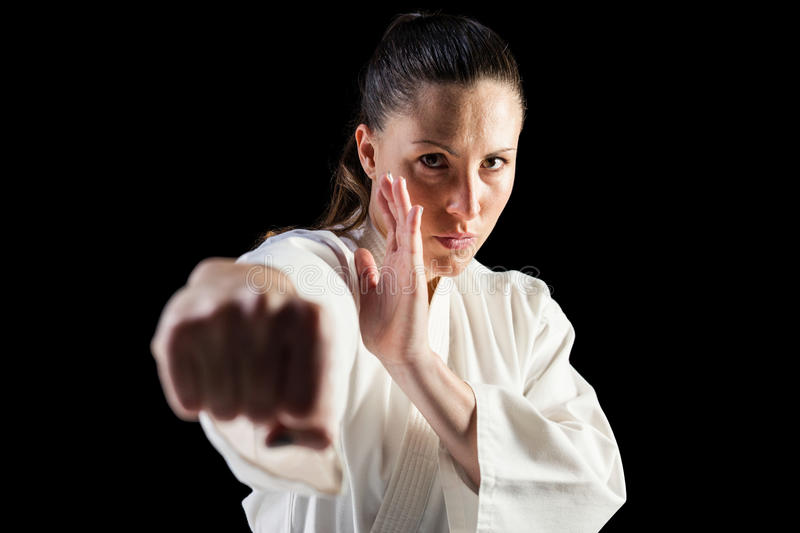 Female fighter performing karate stance. On black background stock photo