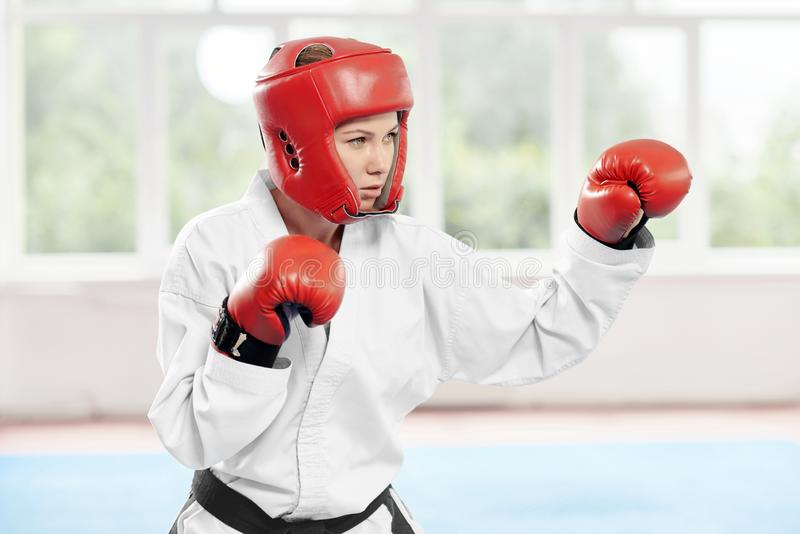 Female fighter performing kick improving technique of fight. royalty free stock photography
