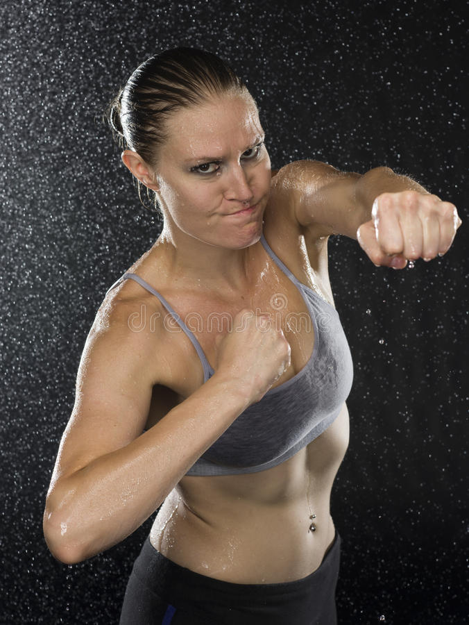 Female Fighter in Punching Pose Looking Aggressive. Half Body Shot of a Female Fighter in Punching Pose Looking at the Camera with Aggressive Facial Expression royalty free stock photos