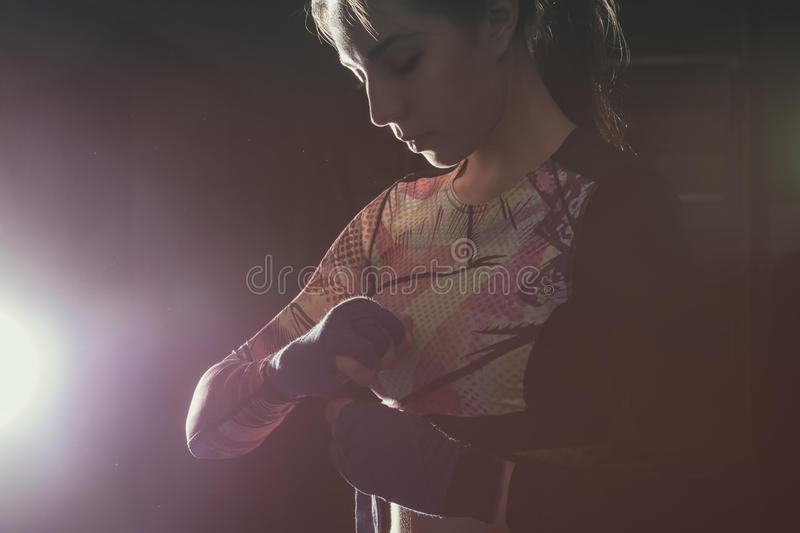 Female fighter putting on boxing gloves prepairing for training royalty free stock images