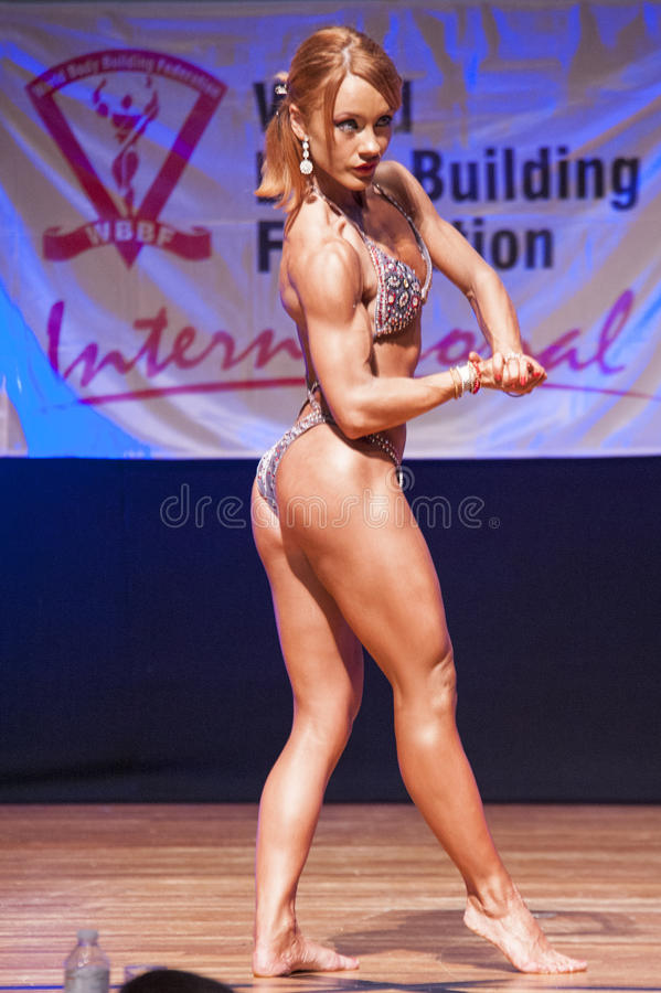 Female figure model flexes her muscles and shows her physique stock photography