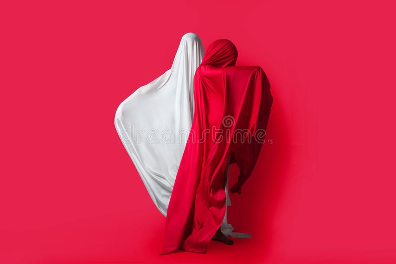 Female figures in fluttering in the wind fabrics. Red and white silhouette on a red background in the Studio. Minimalism. Concept. Female figures in fluttering royalty free stock photo