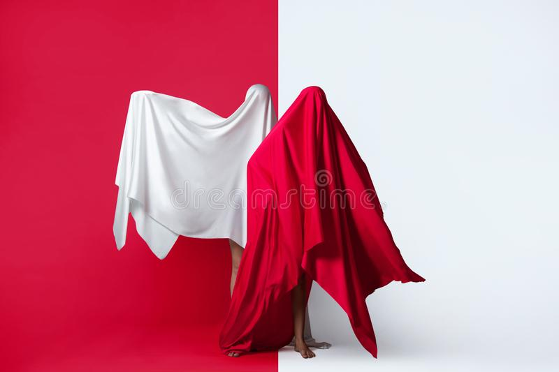 Female figures in fluttering in the wind fabrics. Red and white silhouette on a red background in the Studio. Minimalism. Concept. Female figures in fluttering royalty free stock photography