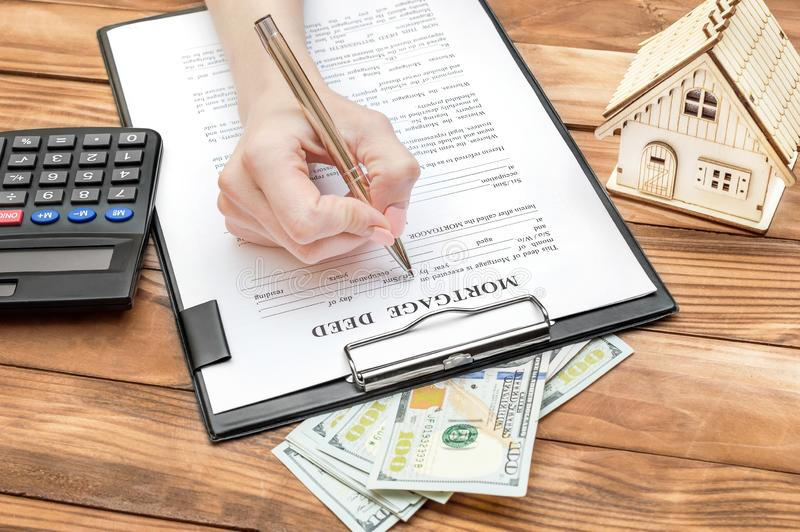 Female filling mortgage deed on the table with model of house, money and calculator. Business concept royalty free stock image
